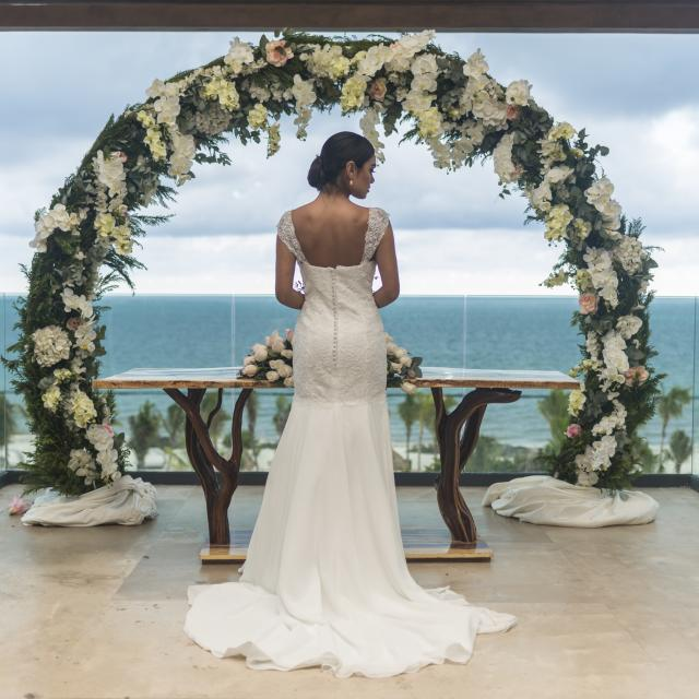 Bride in front of elaborate floral arrangement