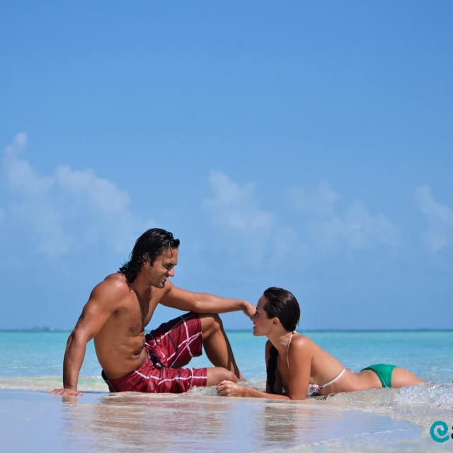 Couple Sitting and Laying on Beach