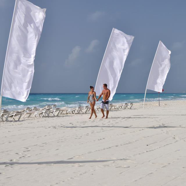 Couple Walking on Beach with White Flags