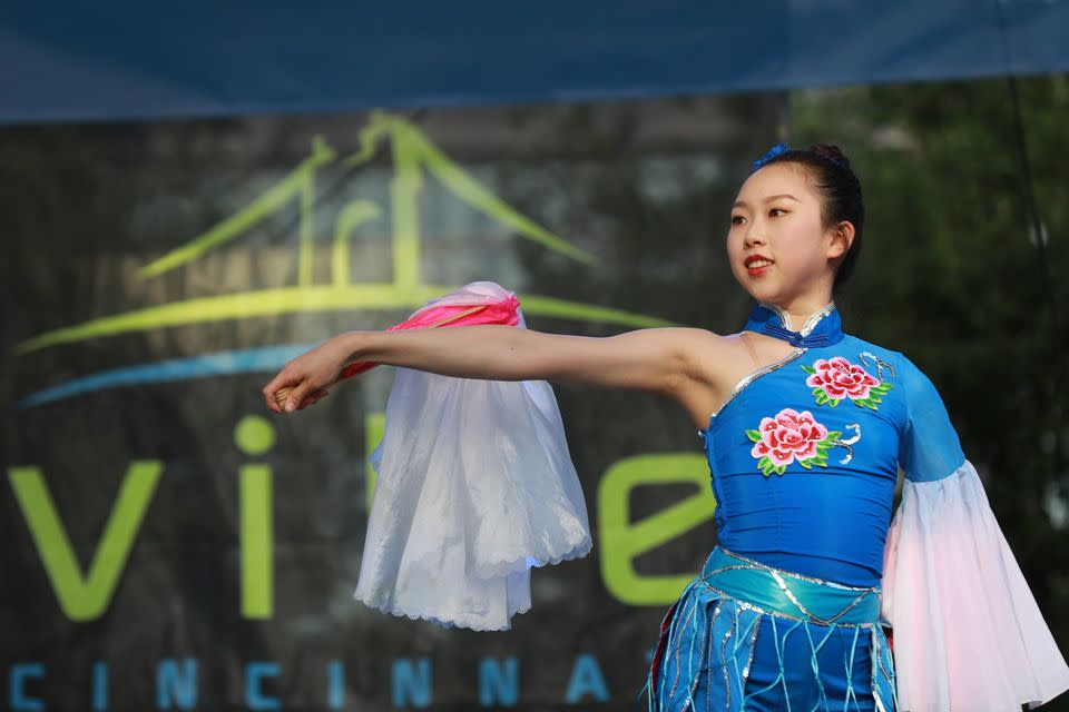 Young Asian woman in a blue dress with red flowers in front of a sign that reads Vibe Cincinnati