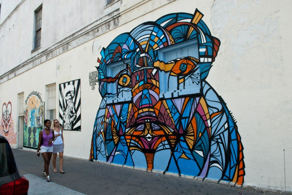Two women walking past rotating mural outside of Mexic Arte Museum in Austin Texas