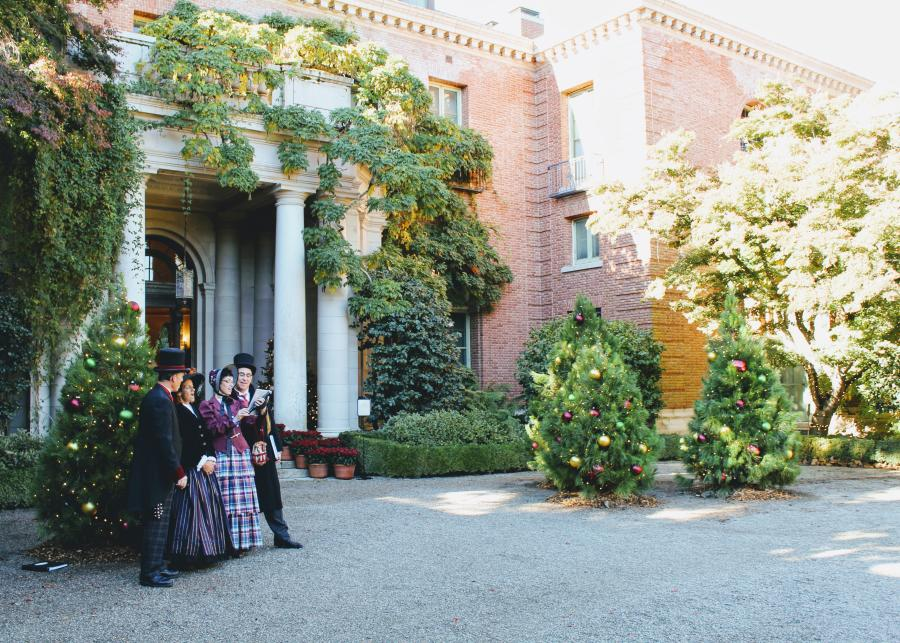 Carolers singing in front of the Filoil Mansion Entrance during the holidays.