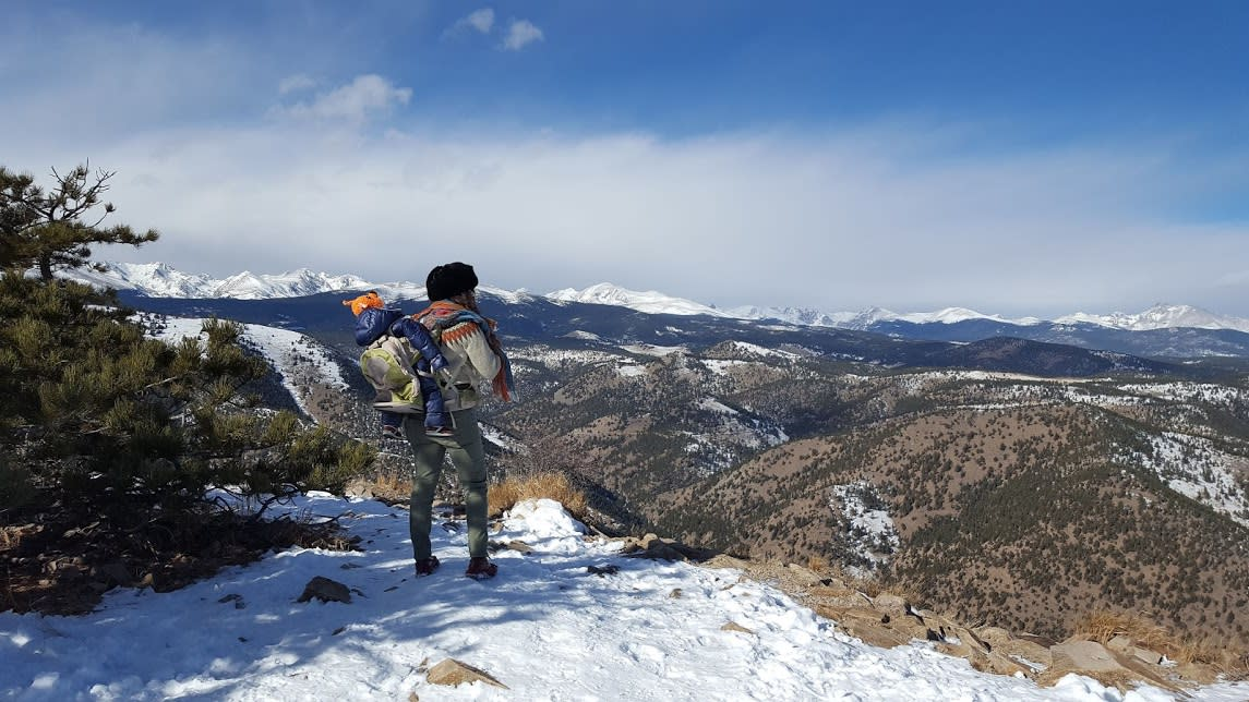 Hiker with a baby backpack overlooking the Boulder valley in the Winter