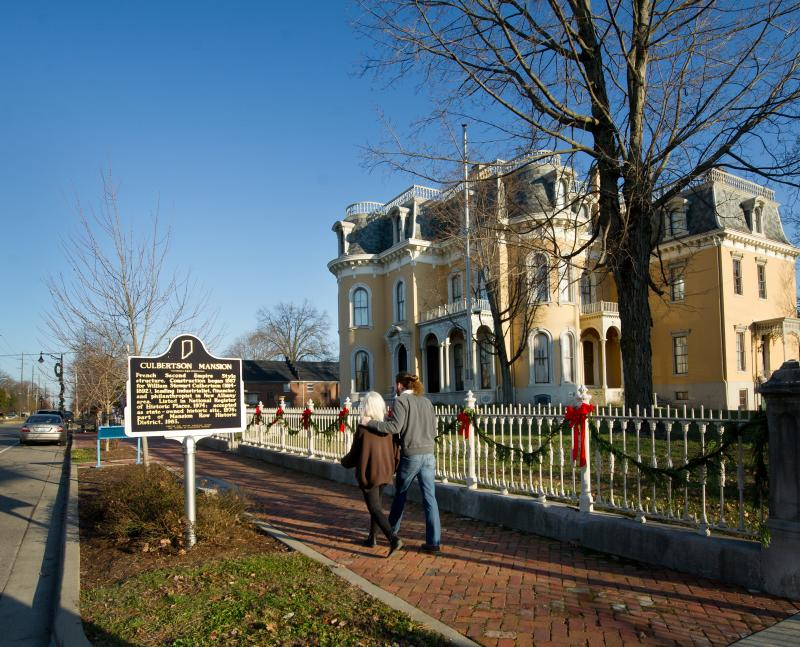 Man and woman walking down the sidewalk outside of Culbertson Mansion during winter