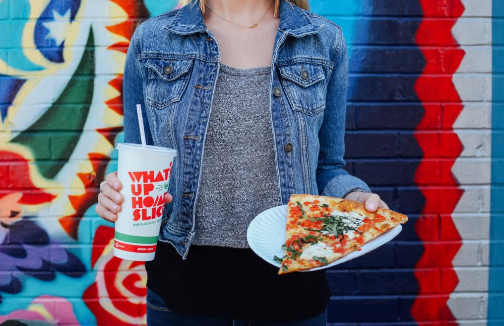 Woman holding a slice of pizza and a soda outside of Home Slice Pizza on South Congress