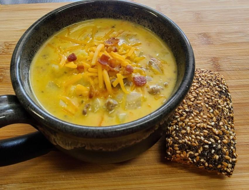 A mug of soup topped with bacon and a side of seeded bread