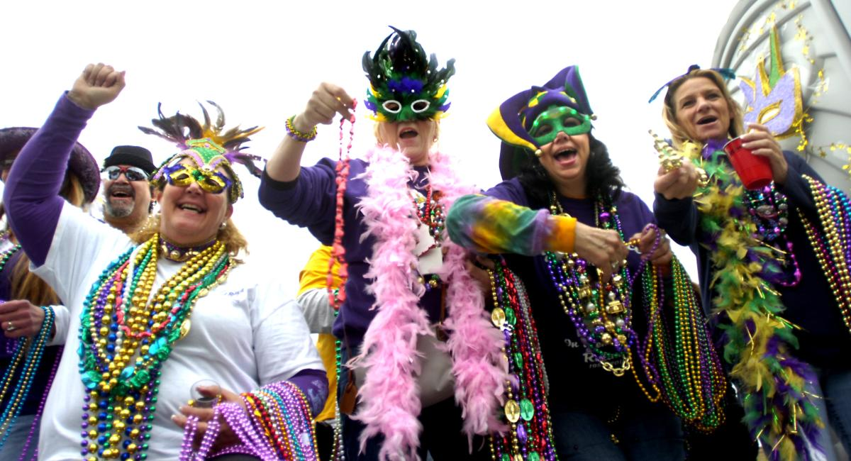 People dressed with masks and beads for Mardi Gras