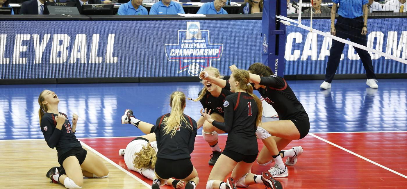 NCAA DI Women Volleyball players celebrate on the court