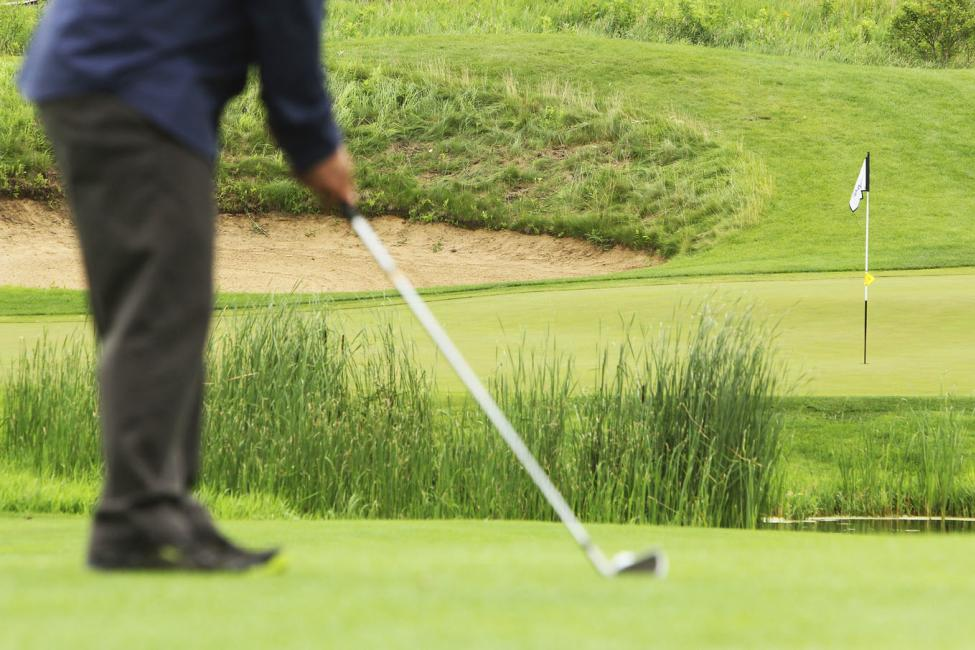 Man hitting a ball on a Chippewa Valley golf course