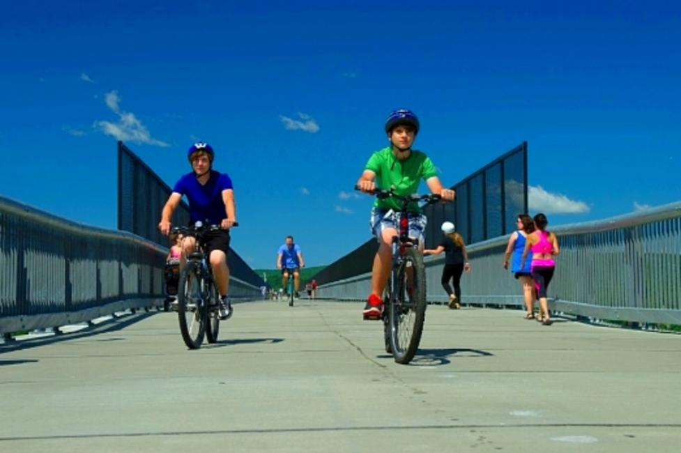 80c396d79a3 Bicyclists cruising across the walkway over the Hudson River