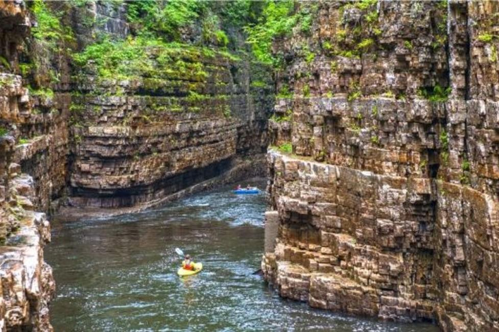 A picture of a person kayaking in the Ausable Chasm River