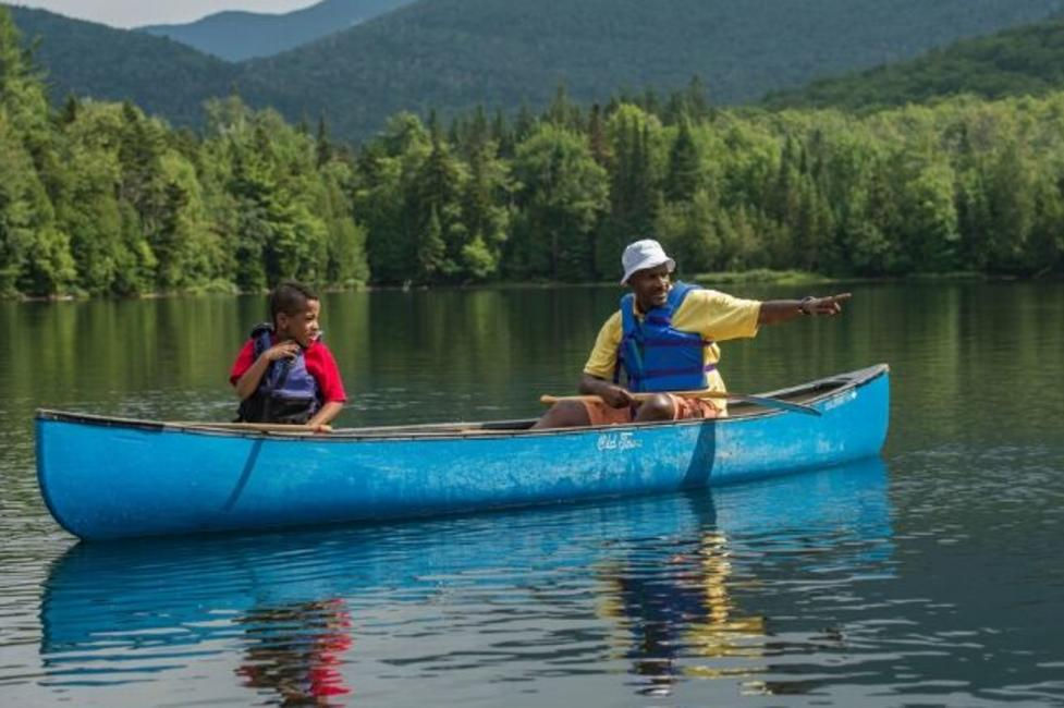 A boy and a man canoe on Heart Lake in the Adirondacks