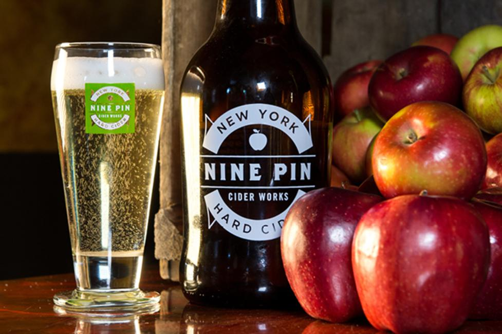A photo of cider in a Nine Pin Coder Works glass next to some red apples