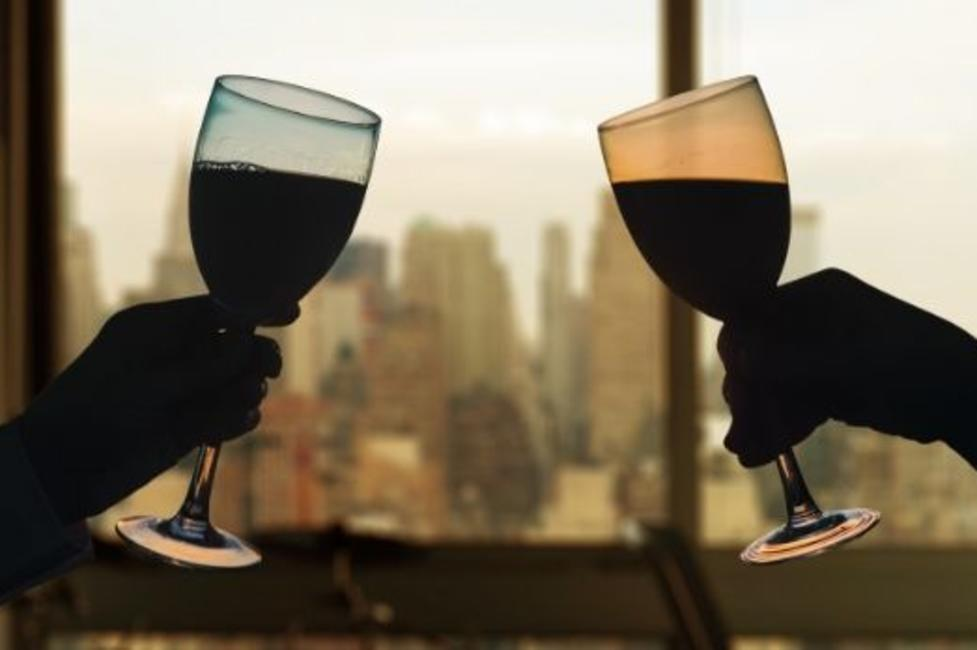 Two wine glasses about to clink with background view of Manhattan