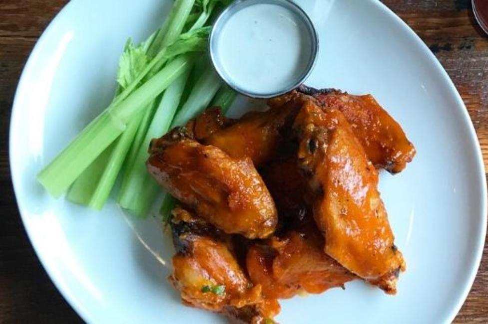 A plate of Buffalo wings with celery and blue cheese sauce