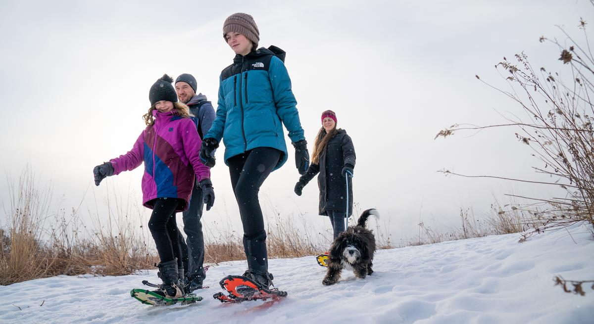 A family and their dog snowshoeing on a trail at Pheasant Branch Conservancy