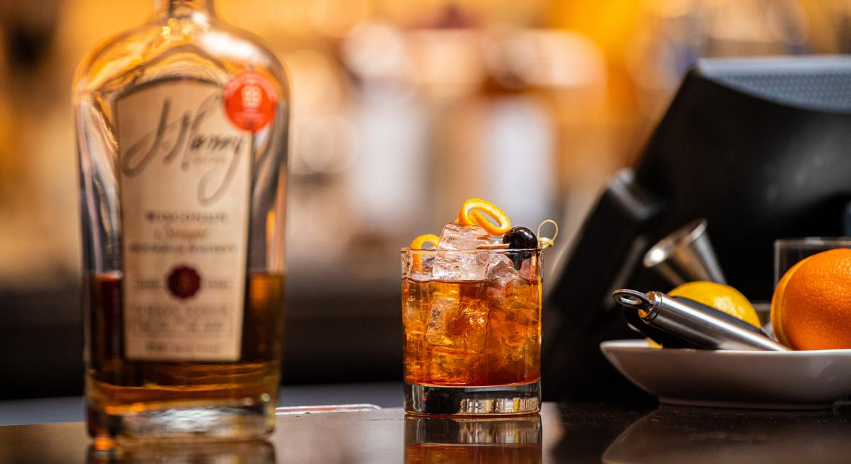 A bottle of J. Henry & Sons bourbon sits next to a hand-crafted cocktail