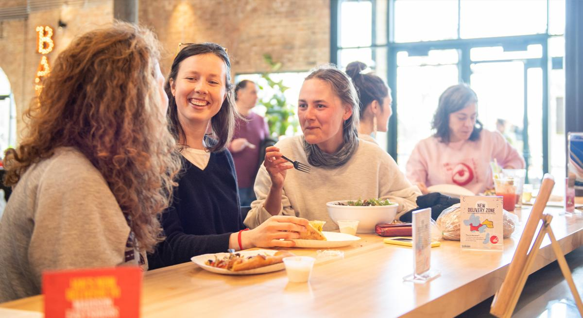 Three women share a laugh while enjoying Ian's Pizza at Garver Feed Mill