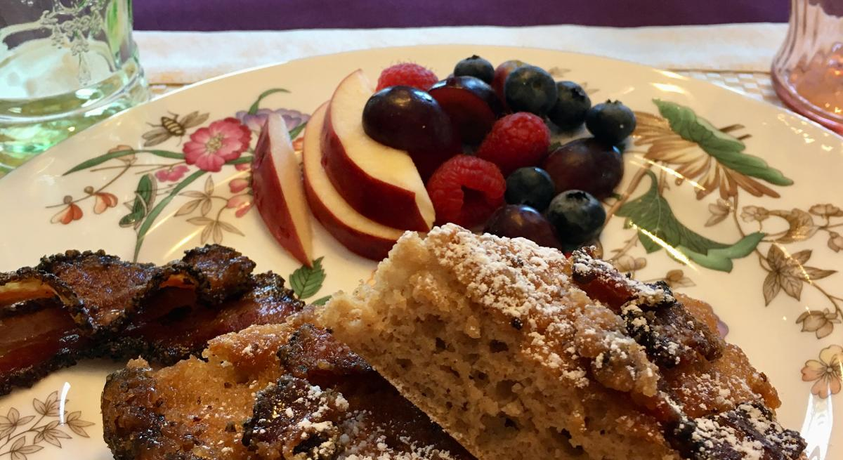 A plate of fresh fruit among other breakfast food items