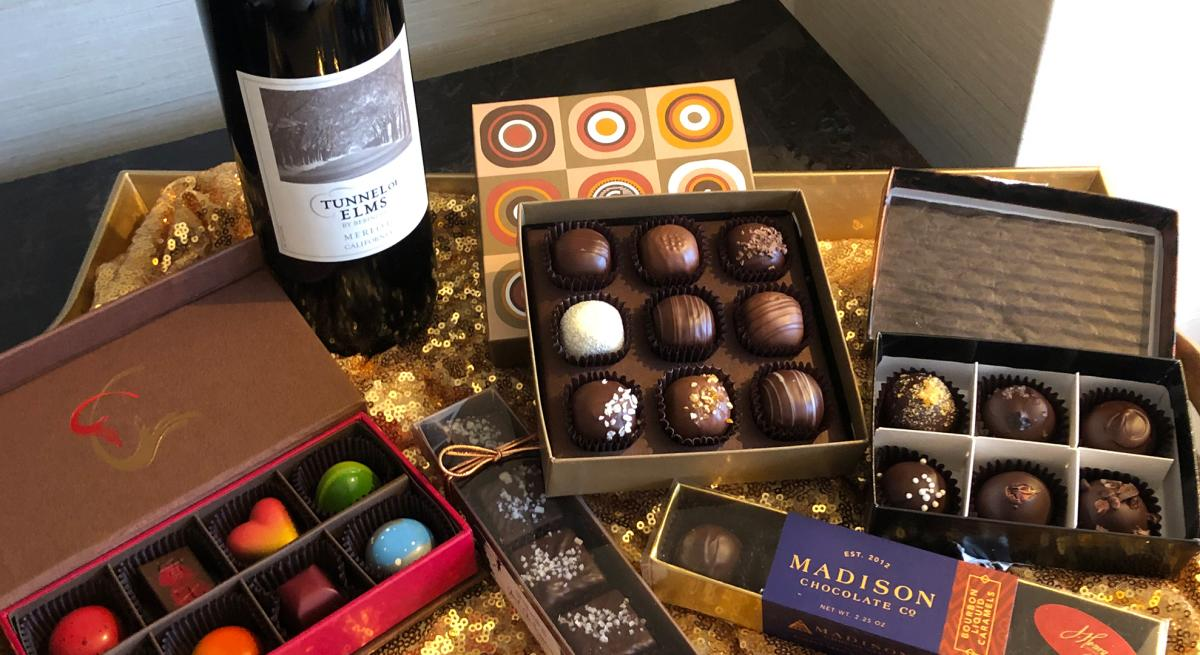 A spread of chocolates and bottle of wine laid out on a table