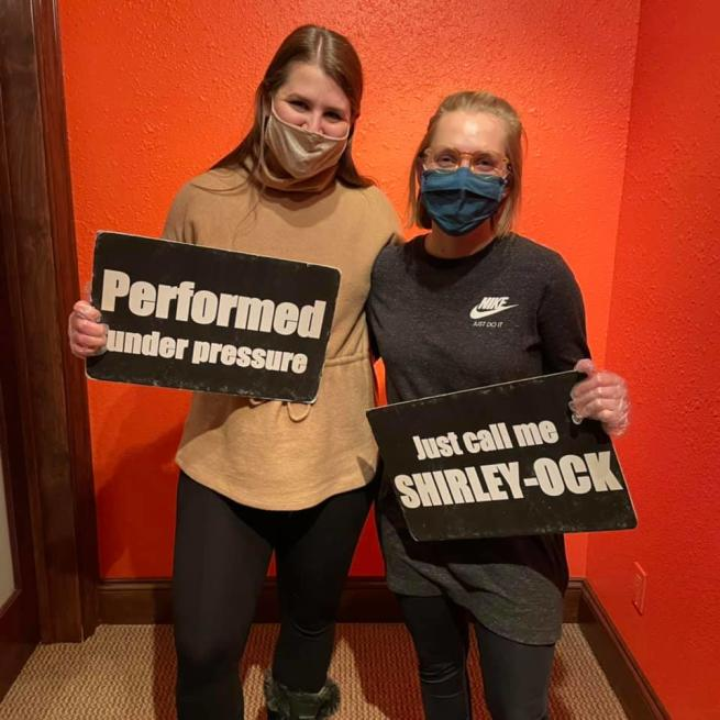 Two women holding signs after completing an escape room at Escape This