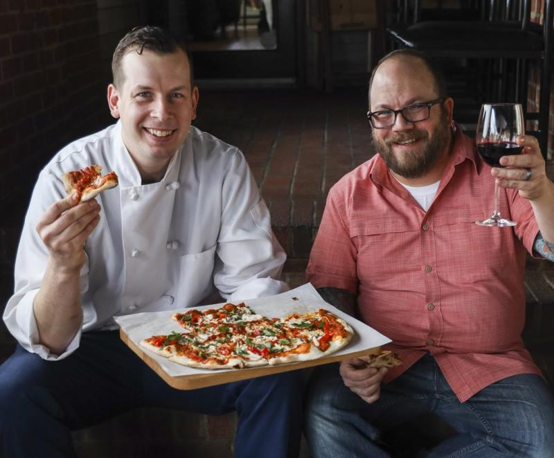 Owners of Vin 909 with pizza and wine