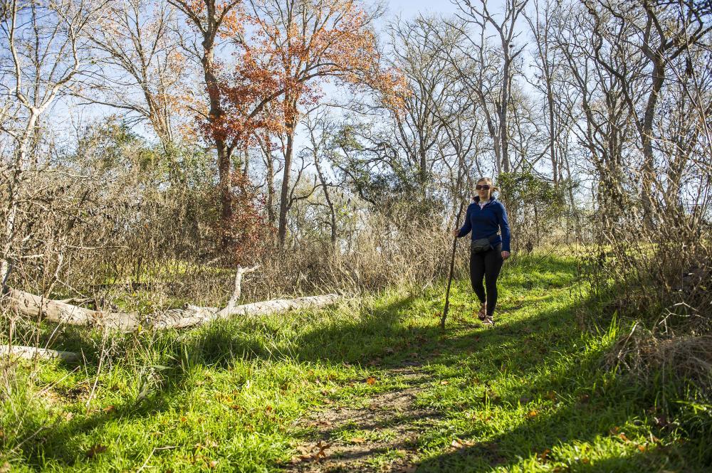 Women walks with hiking stick on trail at Lockhart State Park near Austin Texas