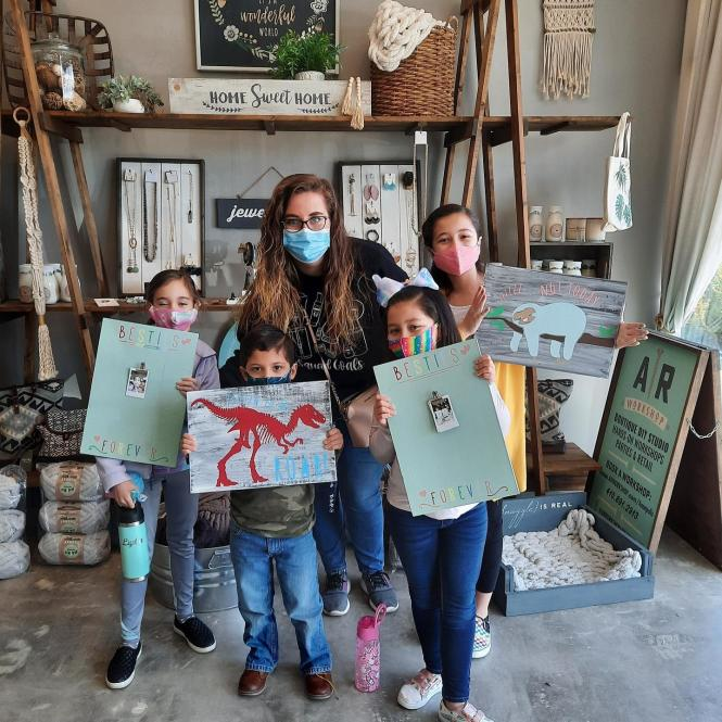 A group of kids show off their art work at AR Workshop.