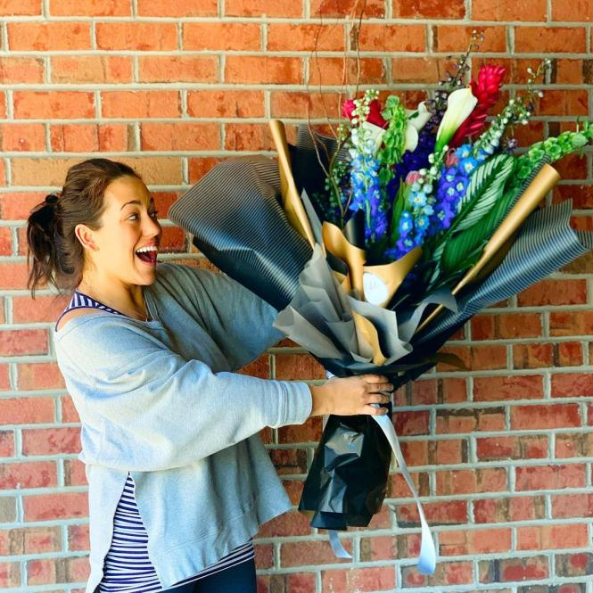 A happy girl with a large bouquet of flowers.