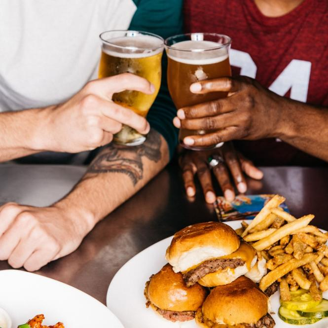 Sports fans toast over burgers and beer.