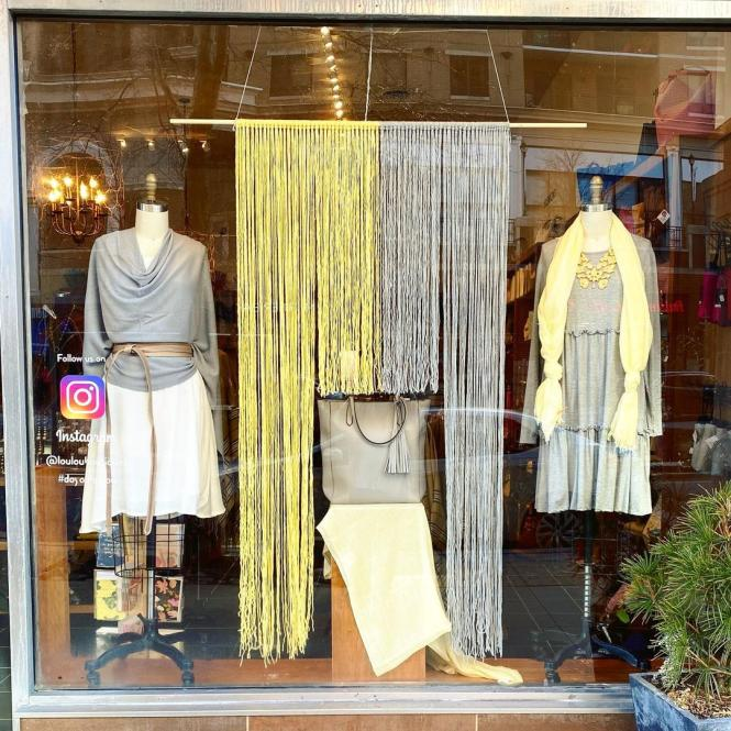 A window display of gray and yellow clothing at lou lou boutiques.
