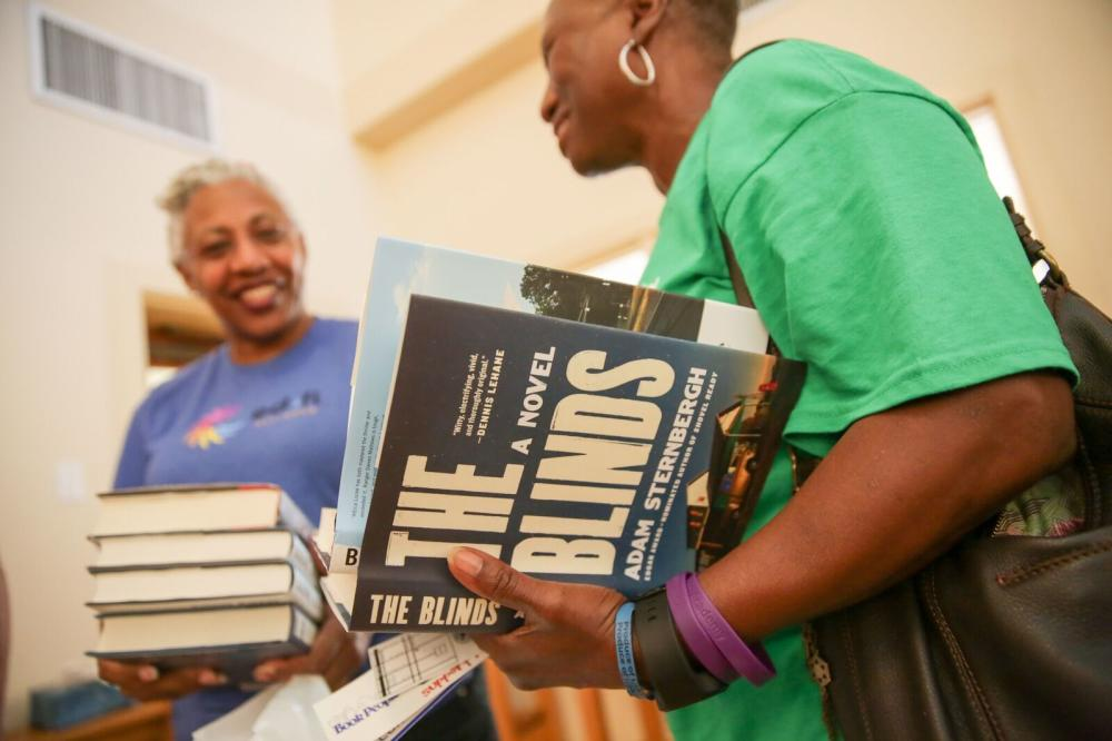 two women stand together one holds book titles The Blinds A NovelTexas Book Festival