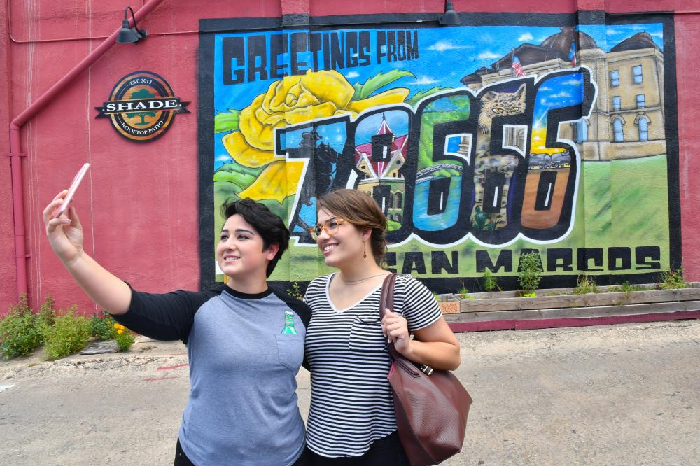 Couple takes a selfie in front of the Greetings from 78666 mural in Kissing Alley in downtown San Marcos.