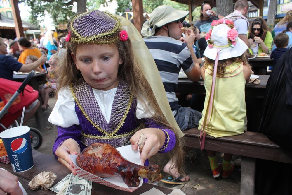 A young girl sits at a table with a giant turkey leg at the Renaissance Faire