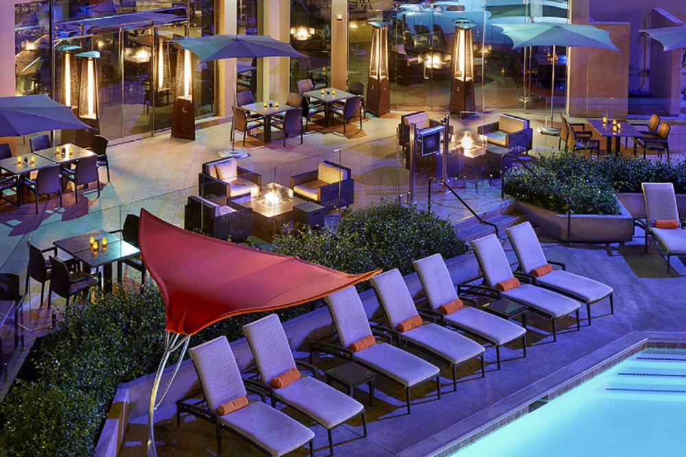 Image of the pool area at the Anaheim Marriott. Image is of a portion of the pool surrounded by eight pool lounge chairs, with restaurant tables in the background.