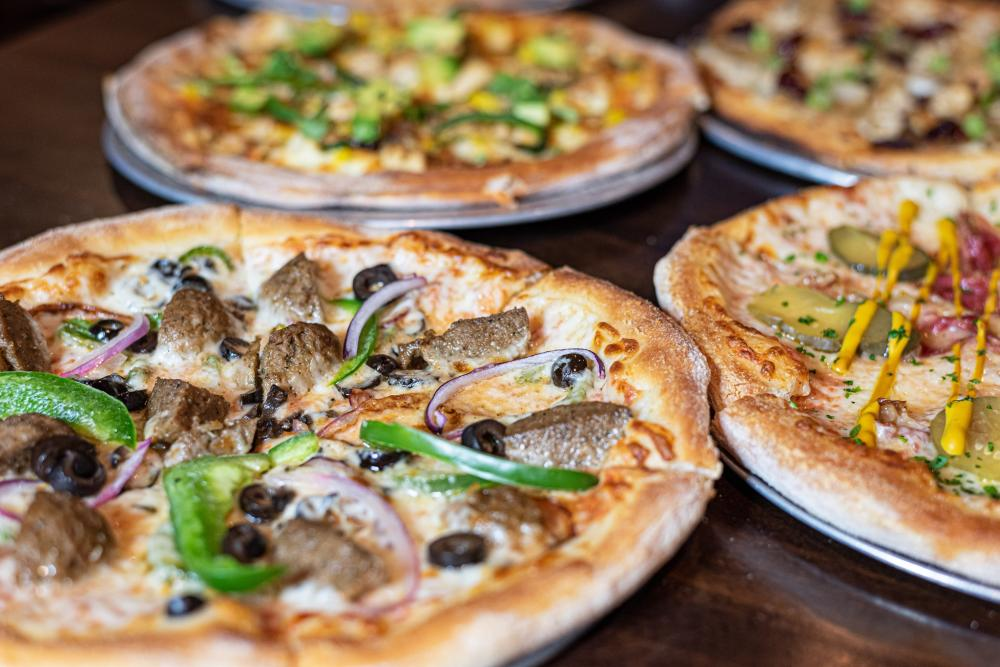 Image of four pizzas laid side-by-side on a wooden table.