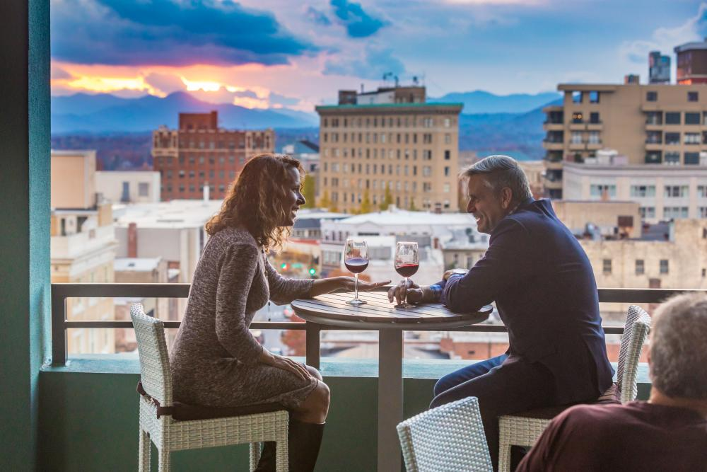 Couple enjoys glasses of wine atop the AC Hotel rooftop balcony.