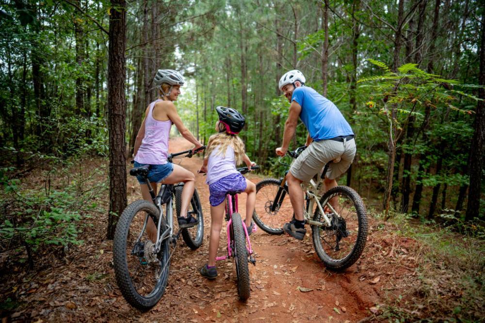A family mountain biking through the woods near Athens, GA
