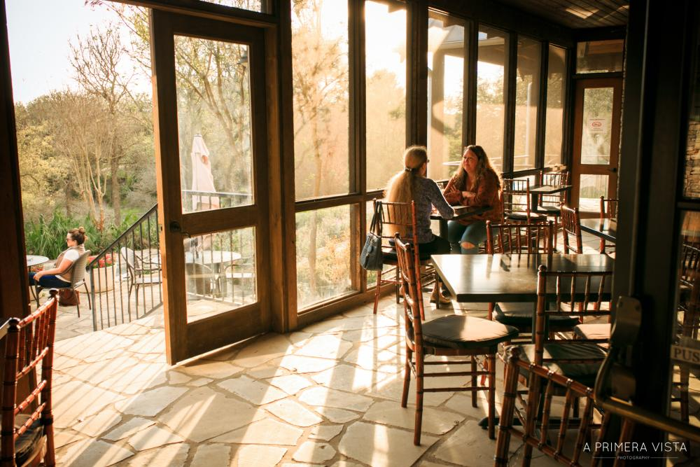 Two women having a wine tasting on screened in patio at Fall Creek Vineyards in Driftwood Texas