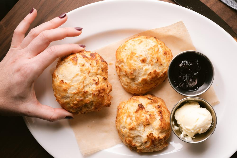 Photo of a hand holding a homemade biscuit from Corinne restaurant, there are two other biscuits on the plate along with a silver bowl of butter and another silver bowl with a dark jam