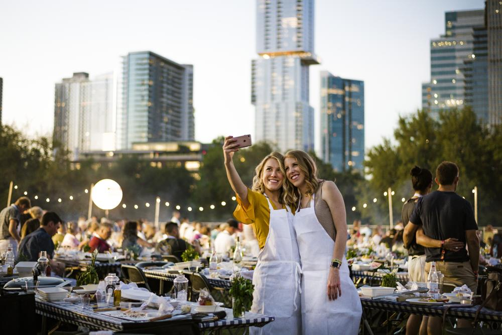 Two women take a selfie in front of skyline at Austin Food and Wine Festival
