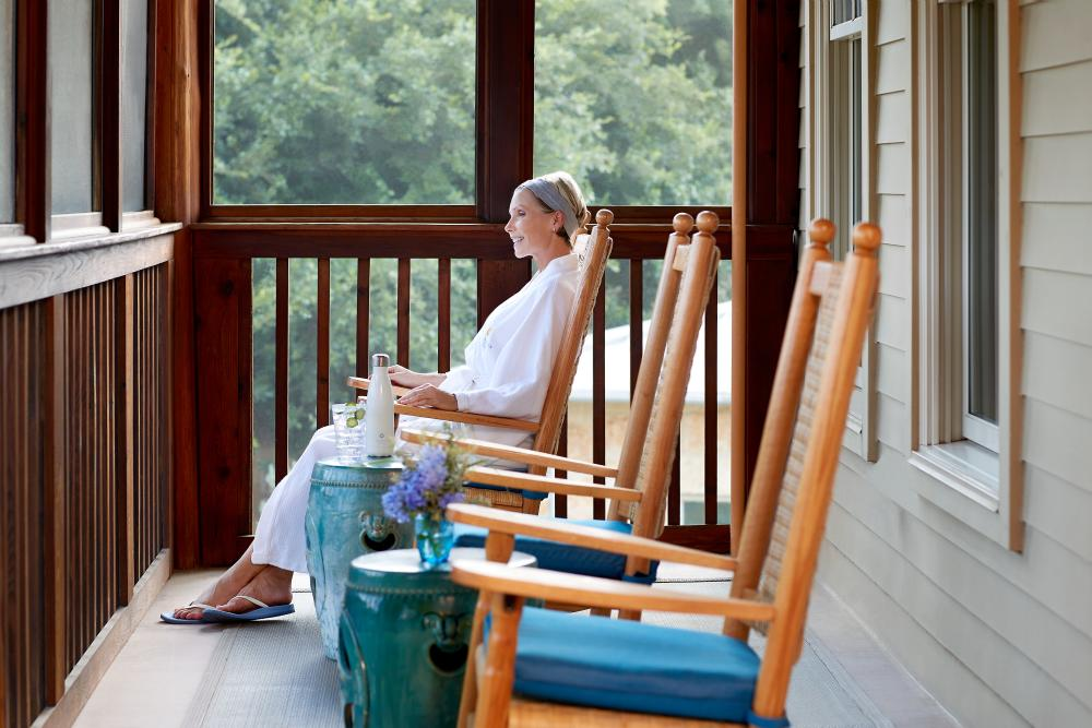 Woman in robe sitting in rocking chair on screened patio at Lake Austin Spa Resort