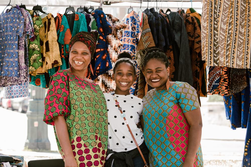 Three women in front of colorful garments at the outdoor Black Makers Market in Austin Texas