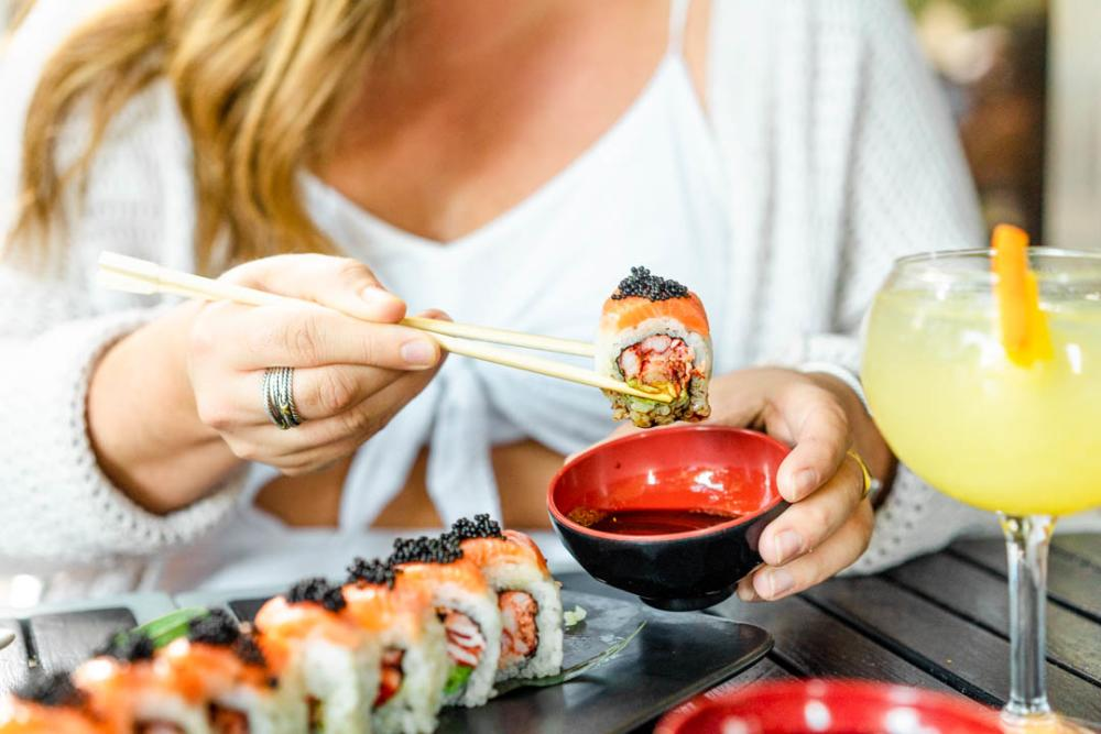 Woman holding sushi with chopsticks at restaurant in the 2ND Street District in Austin Texas