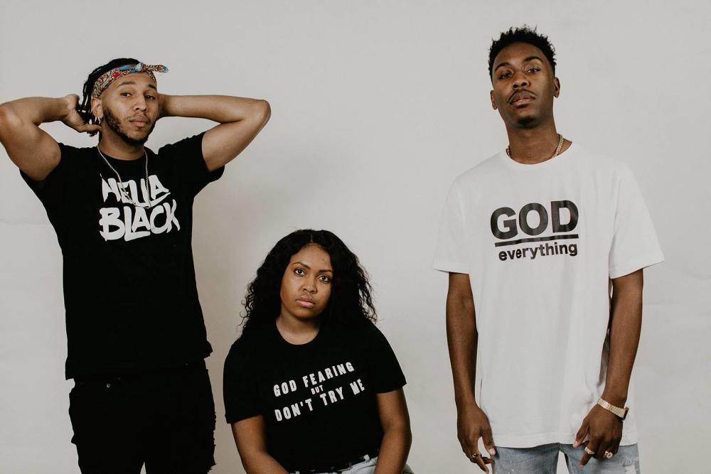 three models wearing Up SZN apparel shirts reading hella black and god fearing but dont try me and god everything