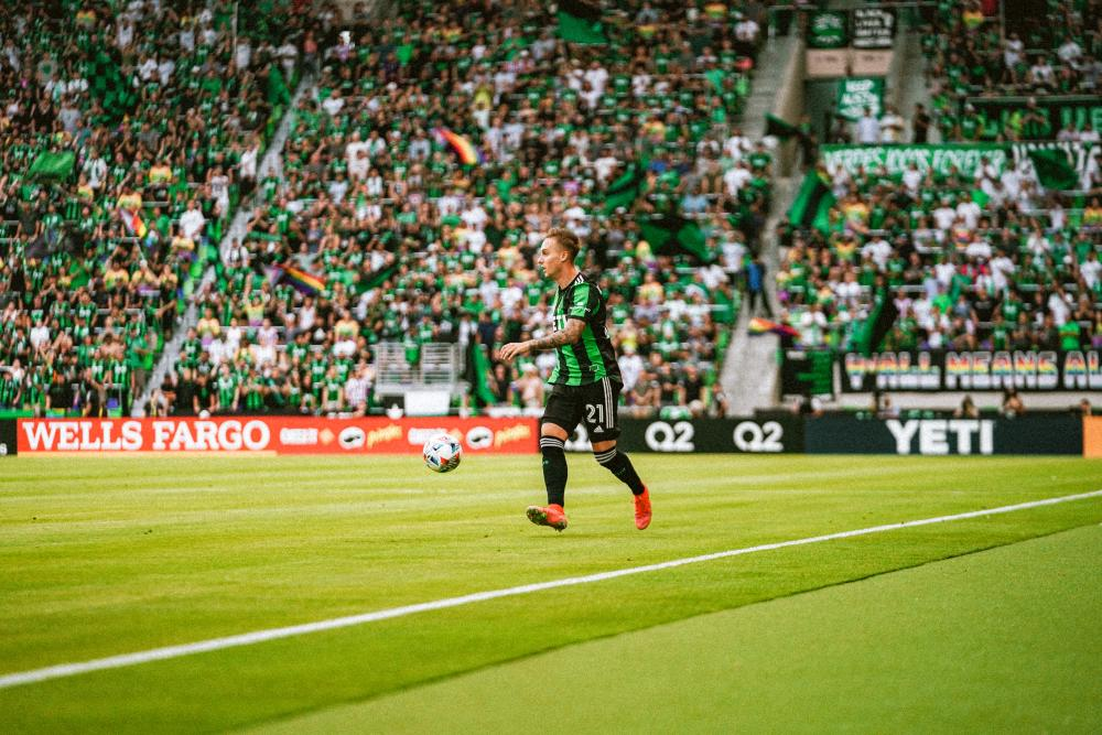 Žan Kolmanič for Austin FC on the field with the ball at Q2 stadium. A large crowd in the Supporters Section is visible behind him, waving rainbow flags