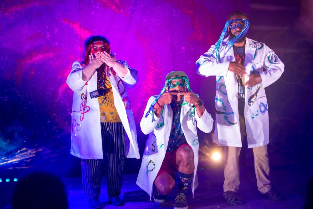 Photo of a performance of Annie Jump and the Library of Heaven at VORTEX theater. Three actors are pictured, all wearing lab coats and dressed as mad scientists