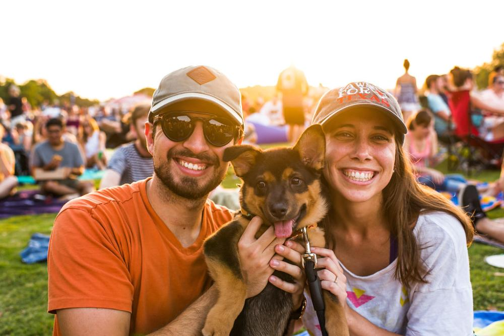 A man and woman holding a german shepherd puppy smile at the camera during ACL Radio's Blues on the Green. They are sitting on a blanket in Zilker Park