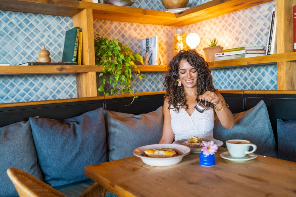 Photo of woman sitting at corner table surrounded by blue cushions in Cafe No Se pouring syrup on pancakes. There is a cup of coffee, a flower and another dish on the table