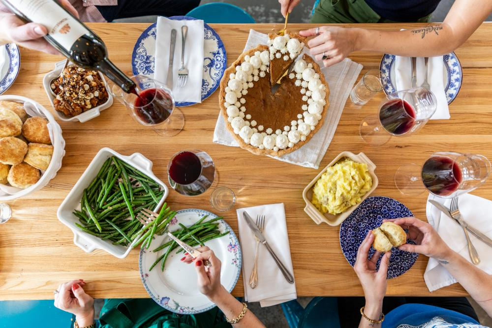 Family style table spread with wine and green beans and pie at Colleens Kitchen in Austin Texas